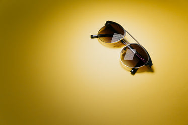 black round sunglasses on top right of yellow background