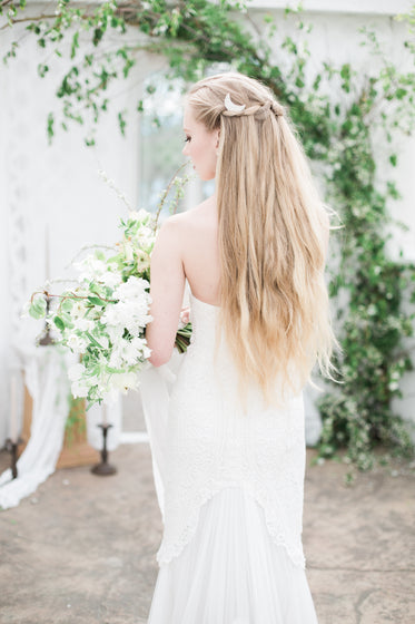 blond person in a white dress holds a large bouquet of flowers