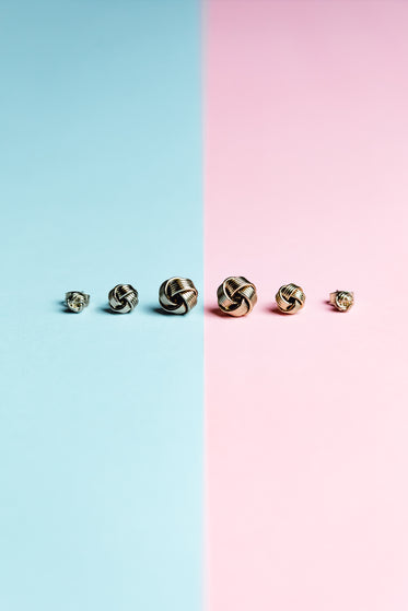 blue and pink background with earrings in a line