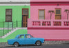 blue car parked next to a green and pink building