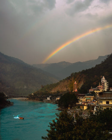 blue river between two hills with a vivid rainbow arching above