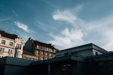 blue skies with wispy clouds over building rooftops