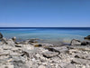 blue sky clear water and rocky shore