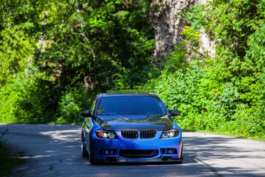 blue sports car drives along country road