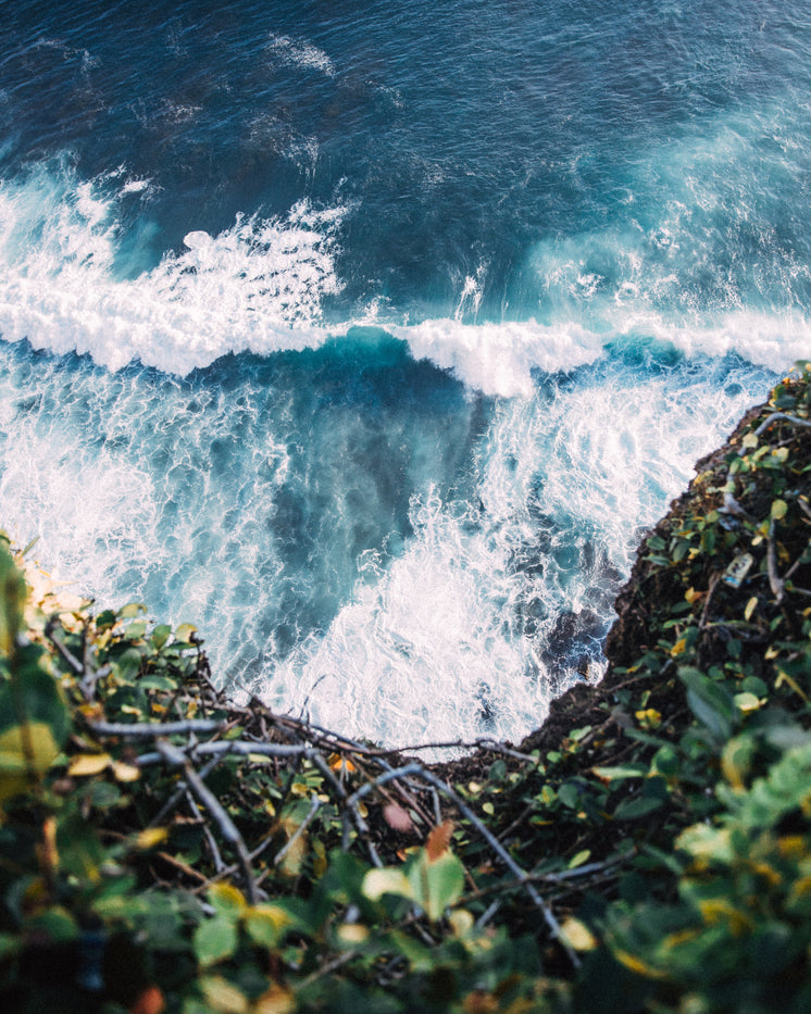 blue-waves-crash-at-base-of-cliff.jpg?wi