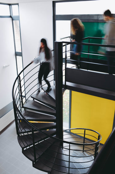 blurred students rush down spiral stairs