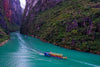 boat travels along river between luscious green mountains