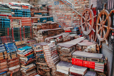 books stacked high against a brick wall