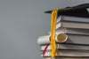 books with graduation cap and diploma