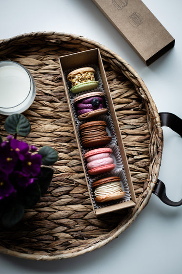box of macarons on a wicker tray
