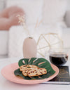 breakfast biscotti lays on a monstera leaf on a pink plate