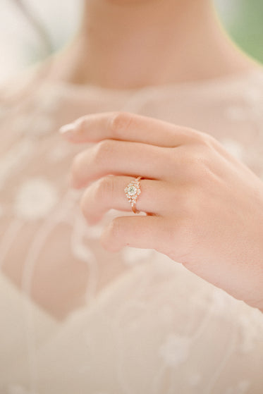 bride holds up wedding ring
