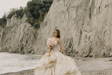 bride in wedding dress by cliffs and beach