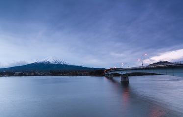 bridge over still water reaches to a large snowy mountain