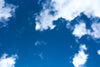 bright blue sky dotted with fluffy white clouds