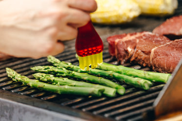 brushing cooking oil on bbq asparagus