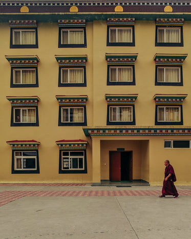 buddhist monk walks by yellow building