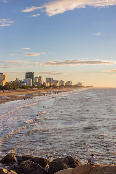 busy beach with city buildings surrounding the coastline