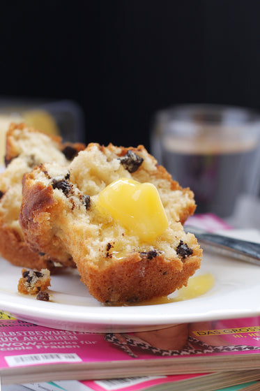 butter melting on warm muffin over coffee and magazines