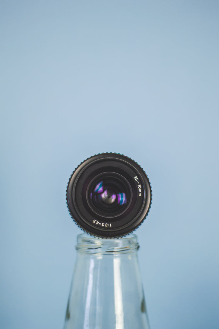 Camera Lens Propped On A Bottle