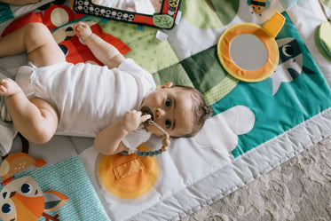 camera looks down to a baby laying in a colorful mat