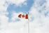 canadian flag against cloudy sky