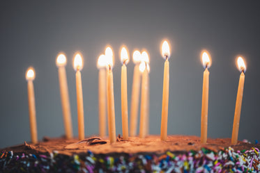 candles on an illuminated chocolate cake