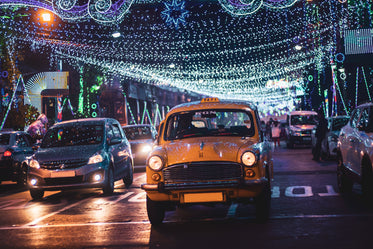 cars on a lit up city street at night