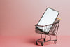 cell phone sits in a small shopping cart against pink