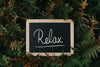 chalkboard sits in green and brown ferns and reads relax