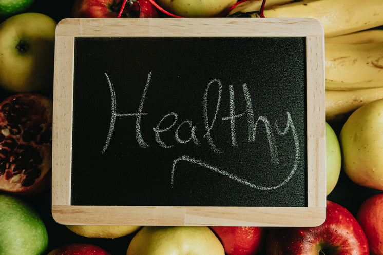 Chalkboard With The Words Healthy In Cursive Lays On Fruit