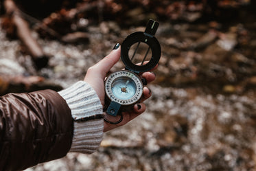 checking a compass on a hike through the woods