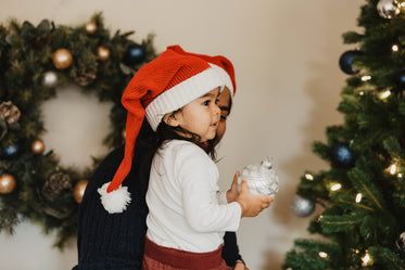 child helps decorate christmas tree