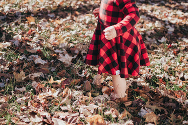 child stands in leaves