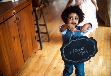 child with i love mom sign