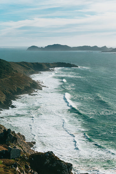 cliff side view of wavy ocean and large hills