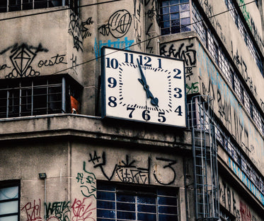 clock on on a building with black graffiti