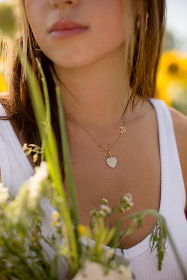 close up of a gold necklace on a person in a white shirt