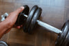 close up of a hand adding weight to a dumbbell