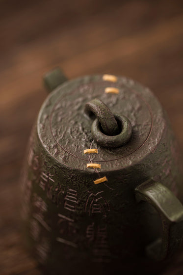 close up of a metal teapot with gold lines