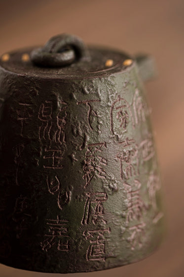 close up of a metal teapot with text carved into it