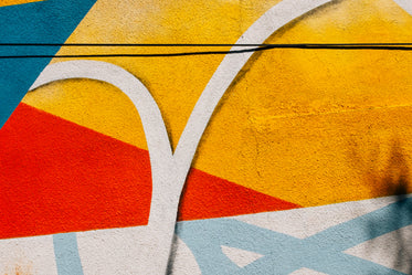 close up of a painted cement wall with splashes of colour