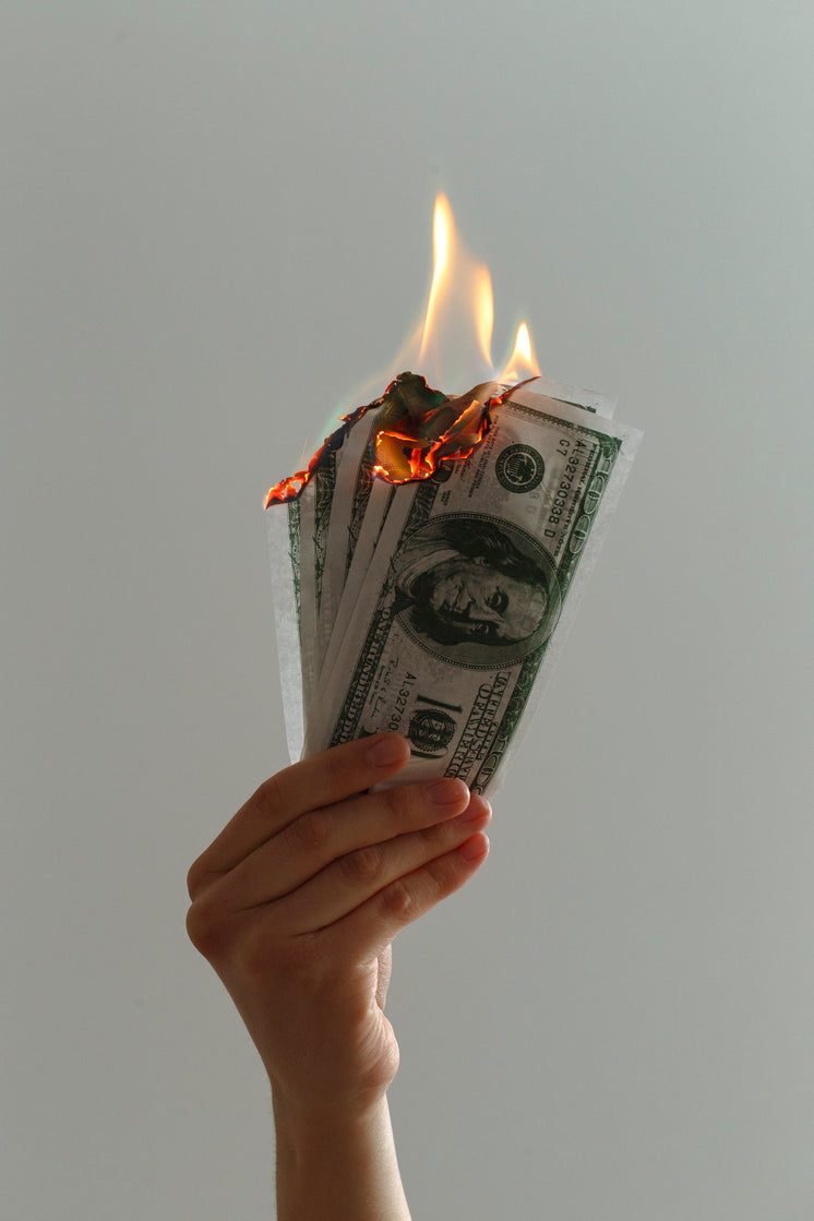 Close Up Of Hand Holding Up Burning Notes