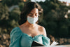 close up of woman reading in a blue face mask