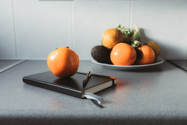 closed notebook with a pen and a persimmon on top of it