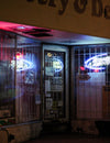 closed store entrance with a bright neon signs