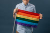 closer up person holding a small pride flag