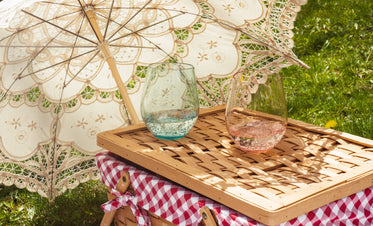 cloth parasol lays on the grass next to a picnic basket