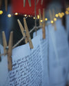 clothes pins holds up white paper with writing