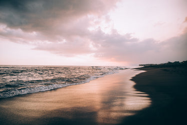 clouds in a pink sky over wave-soaked beach
